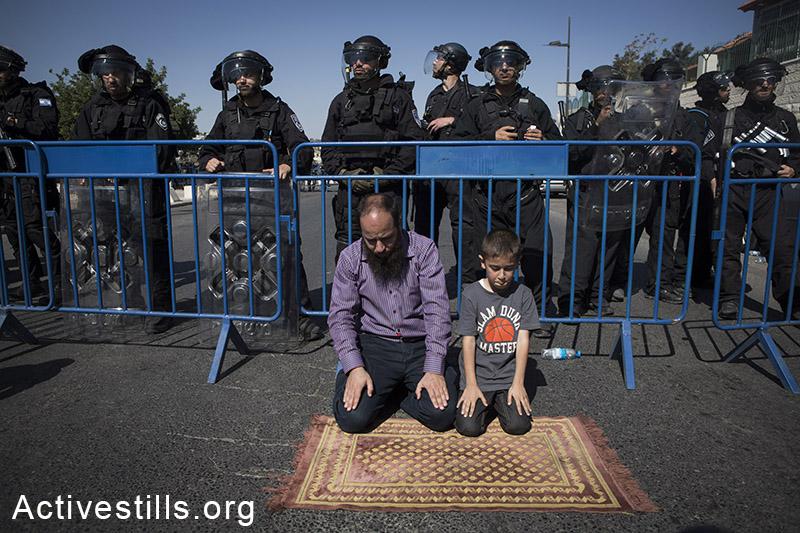 בירושלים, העלמת הפלסטינים היא דרך חיים. פלסטינים מתפללים ליד מחסומי המשטרה מחוץ לאל אקסה באזור ראס אל-עמוד בשל הגבלות הכניסה למתחם המסגד, מזרח ירושלים, 24 אוקטובר, 2014. (אקטיבסטילס)