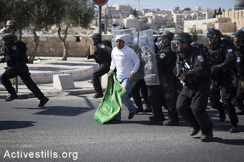 שוטרים הודפים מתפלל בסוף התפילה הרחק מאזור אל-אקסה, במהלך תפילות יום השישי, ראס אל-עמוד, מזרח ירושלים, 24 אוקטובר, 2014. המשטרה הגבילה כניסת מתפללים מתחת לגיל 40. (אקטיבסטילס)
