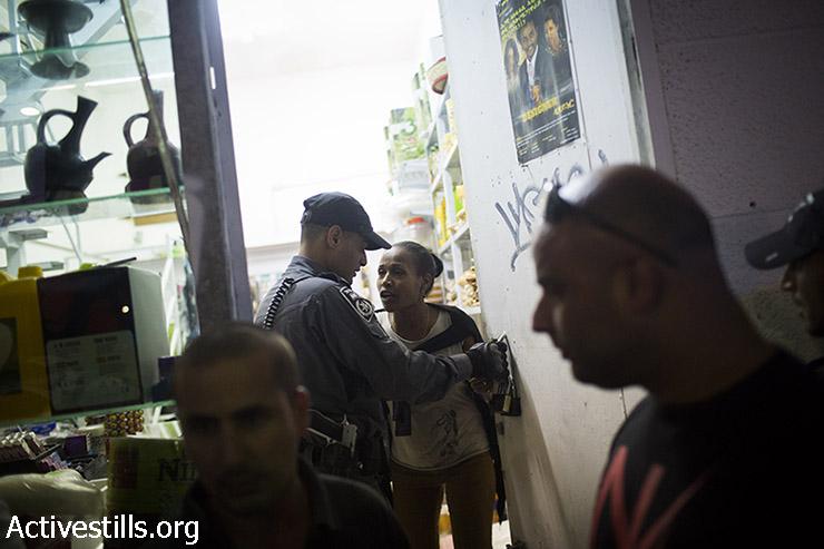 שוטר מאלץ מבקשת מקלט לסגור את חנותה במהלך ההפגנה. (אורן זיו/אקטיבסטילס)