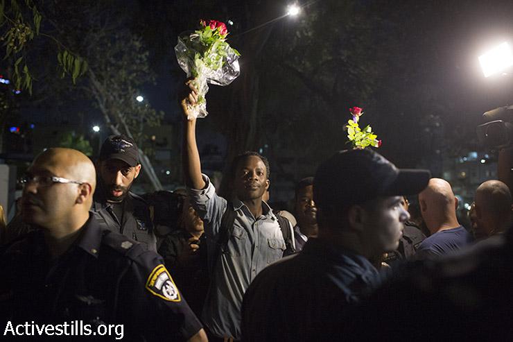 מבקש מקלט מקבל את המפגינים בגינת לוינסקי עם פרחים. (אורן זיו/אקטיבסטילס)