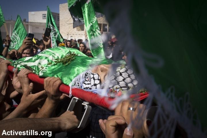 פלסטינים נושאים את גופתו של אורווה חאמד במהלך הלוויתו, סילוואד, הגדה מערבית, 26 אוקטובר, 2014. אורן זיו/אקטיבסטילס