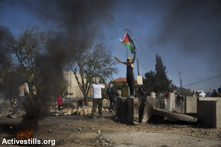 צעיר פלסטיני מניף דגל פלסטין במהלך עימותים לאחר הלוויתו של אורווה חאמד, סילוואד, הגדה מערבית, 26 אוקטובר, 2014. אורן זיו/אקטיבסטילס