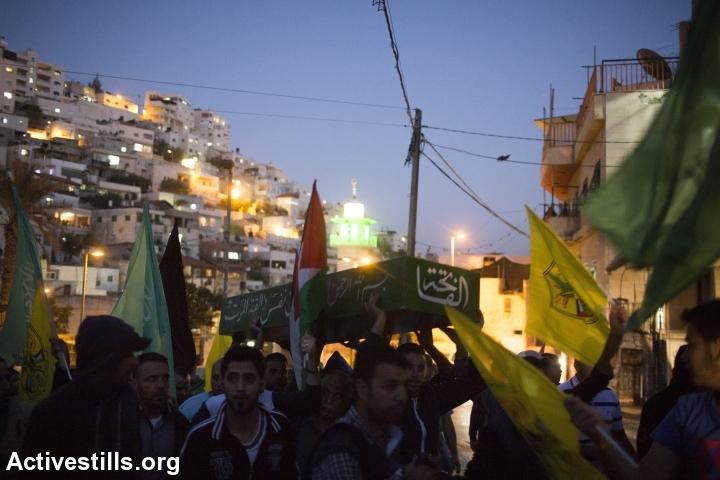 פלסטינים נושאים ארון דמה במהלך הלוויה סימבולית לעבד אל-רחמאן אל-שאלוודי, סילוואן, מזרח ירושלים, 26.10.2014. אורן זיו/אקטיבסטילס