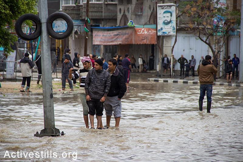 עזתים ברחובות המוצפים של אל-נאפק, העיר עזה, 27 לנובמבר, 2014. באסל יאזורי/אקטיבסטילס