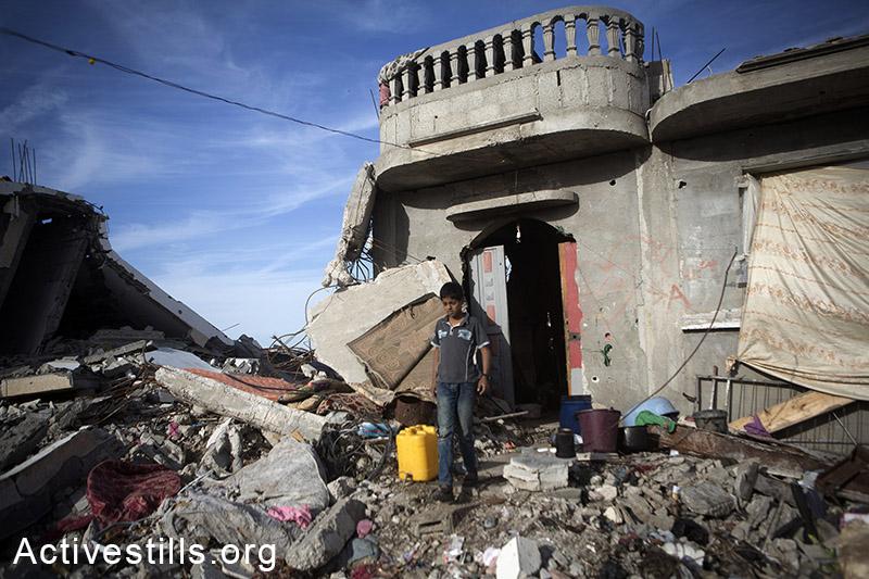 ילד יוצא מביתו ההרוס למלא מיכל במים, כפר קוזאה, מזרח רצועת עזה, 7 נובמבר, 2014. אן פאק/אקטיבסטילס