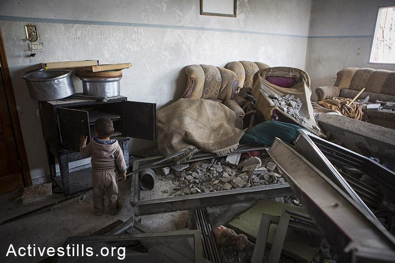 סלון הרוס בבית משפחת טאלאל אל-הילו בשכונת שג׳יעה, מזרח רצועת עזה, 10 נובמבר 2014. אן פאק/אקטיבסטילס