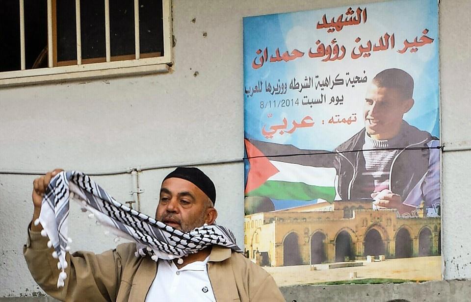 ראוף חמדאן מתאבל על בנו. מאחוריו תמונת הבן עם הכיתוב: ח'יר חמדאן קורבן שנאת המשטרה ושרה לערבים. שבת ה8.11/2014 האישום- ערבי צילום: אבי בלכרמן