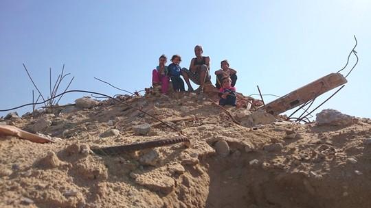 עזה 2014. כמאל וילדיו יושבים על הריסות ביתם השני שנהרס