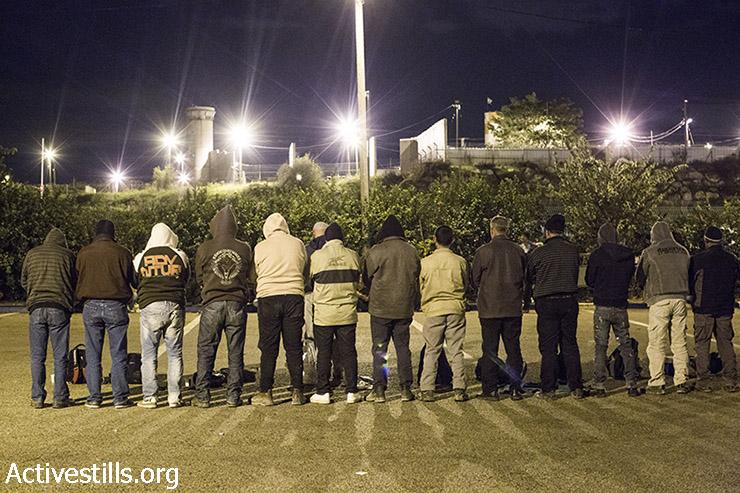 פועלים מתפללים במחסום שער אפרים (קרן מנור / אקטיבסטילס)