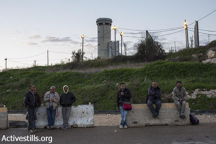 עובדים מחכים להסעה מחוץ למחסום שער אפרים (קרן מנור / אקטיבסטילס)