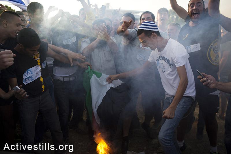 פעילי ימין שורפים דגל פלסטין וקוראים קריאות גזעניות במהלך הפגנה בצומת גוש עציון בעקבות חטיפתם של שלושה צעירים מתנחלים ארבעה ימים קודם לכן. 16 ביוני, 2014. (אורן זיו/אקטיבסטילס)