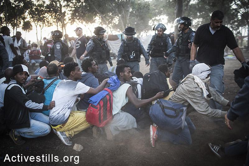 שוטרים עוצרים מבקשי מקלט במהלך ״צעדת חופש״ שנייה של כלואי מתקן ״חולות״ במחאה על כליאתם. 29 ביוני, 2014. כ- 800 מבקשי מקלט יצאו ממתקן ״חולות״ בנגב לכיוון גבול ישראל-מצרים בקריאה אל האו״ם והצלב האדום להתערב במדיניות המקלט של ישראל. בדומה לצעדת החופש הראשונה כל משתתפי הצעדה נעצרו והוחזרו למתקן הכליאה. (אורן זיו/אקטיבסטילס)