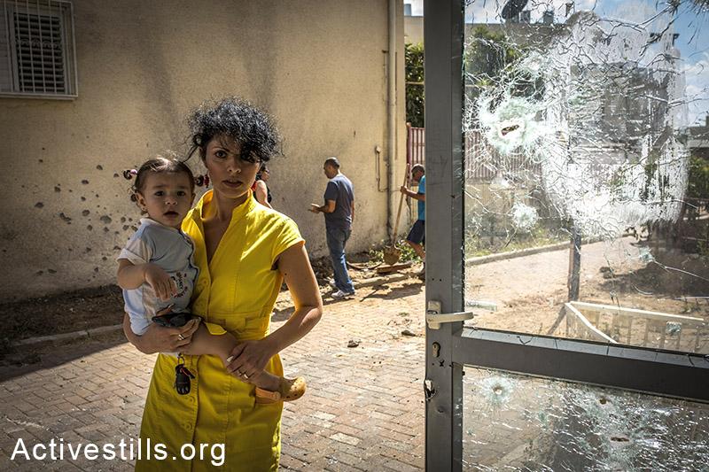 אמא וילד עומדים באזור אשר נפגע ע״י טיל ששוגר מעזה לעיר שדרות ביומו השמיני של המבצע הצבאי ״צוק איתן״ בעזה . 15 ביולי, 2014. (יותם רונן/אקטיבסטילס)