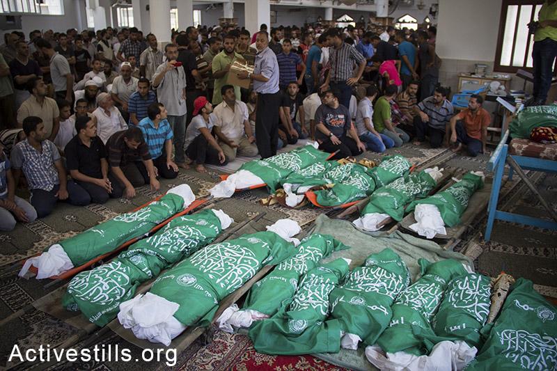הלוויתם של 26 בני משפחת אבו-ג'מעה שנהרגו יום קודם לכן בעקבות הפצצת הצבא בחאן יונס, רצועת עזה, 21 ביולי, 2014. (באסל יאזורי/אקטיבסטילס)