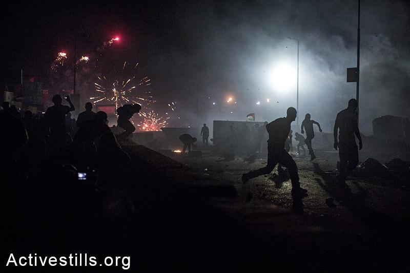 צעירים פלסטינים רצים לתפוס מחסה מירי חי של הצבא בעת עימותים שפרצו במחסום קלנדיה במחאה על ההרג המאסיבי שמבצעת ישראל בעזה. (אורן זיו/אקטיבסטילס)