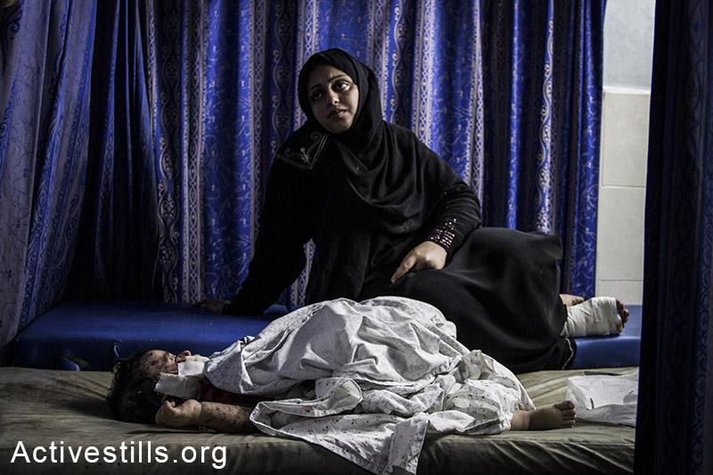 ילד פלסטיני פצוע ואימו בבית החולים שיפא בעזה. 30 ביולי, 2014. (באסל יאזורי/אקטיבסטילס)