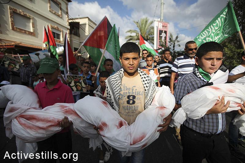 ילדים פלסטינים תושבי ישראל אוחזים בבובות עטופות בתחריכים ומוכתמות בצבע אדום במהלך הפגנה נגד המלחמה בעזה. תמרה, 2 באוגוסט, 2014. (פיאז אבו רמלה/אקטיבסטילס)