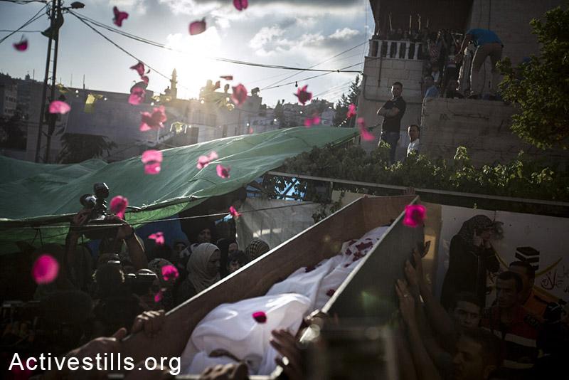 פלסטינים נושאים את גופתו של מוחמד סינוקרות במהלך הלוויתו בשכונת ואדי ג'וז במזרח ירושלים, 8 בספטמבר, 2104. סינוקרות, בן 16, נורה ע״י המשטרה ב-31 באוגוסט ומת מפצעיו. (פיאז אבו רמלה/אקטיבסטילס)