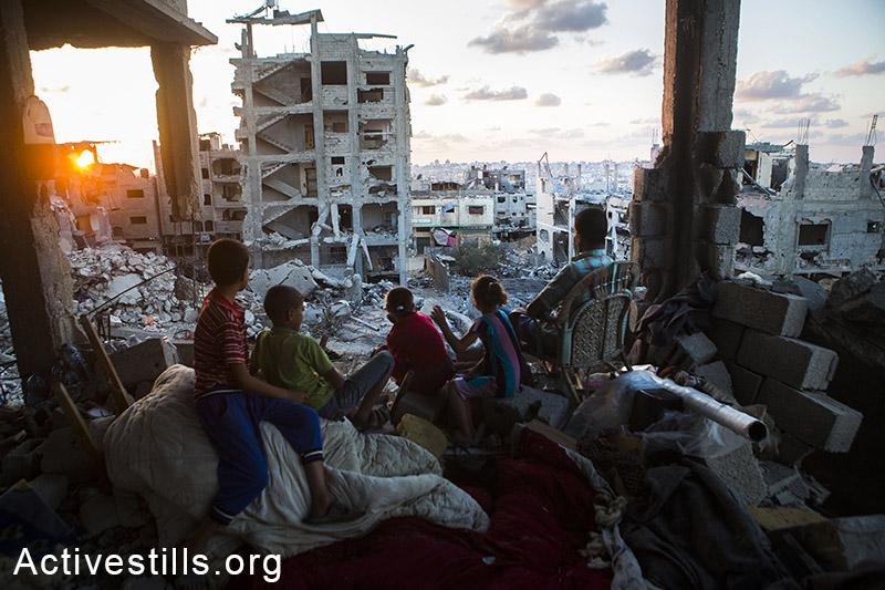 משפחה פלסטינית יושבת בביתה שהופצץ ע״י הצבא ברובע תופח בעזה, 21 בספטמבר, 2014. (אן פק/אקטיבסטילס)