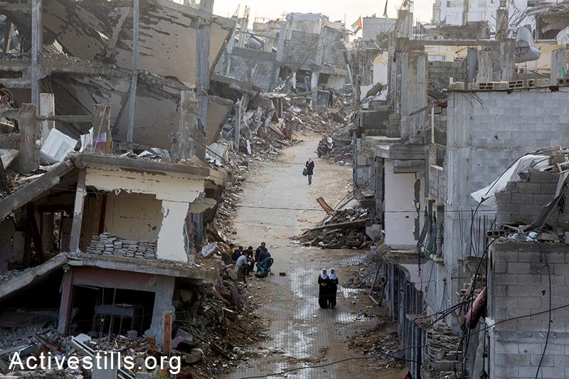 תלמידות פלסטיניות הולכות ברחוב מוצף מי גשמים בשכונת סג'עייה ההרוסה בעזה, 4 בנובמבר, 2014. שבעת שבועות הלחימה בין ישראל לעזה הותירו מעל ל-108,000 פלסטינים מחוסרי בית. כ- 18,000 בתים נהרסו כליל או חלקית בעזה בעקבות הפצצות הצבא. (אן פאק/אקטיבסטילס)