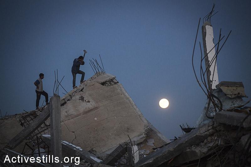 פלסטינים אוספים מתכות מבתיהם ההרוסים בכפר חוזעה שבמזרח רצועת עזה. 6 בנובמבר, 2014. (אן פק/אקטיבסטילס)