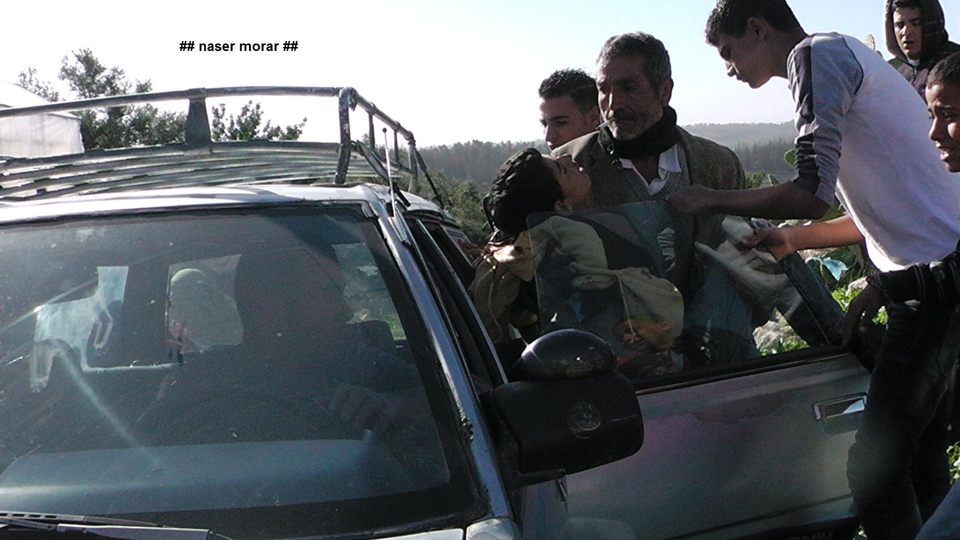 הנער סמיר עווד מפונה לאחר שנורה בגבו על ידי חיילים, בודרוס (נאסר מוראר, בצלם)