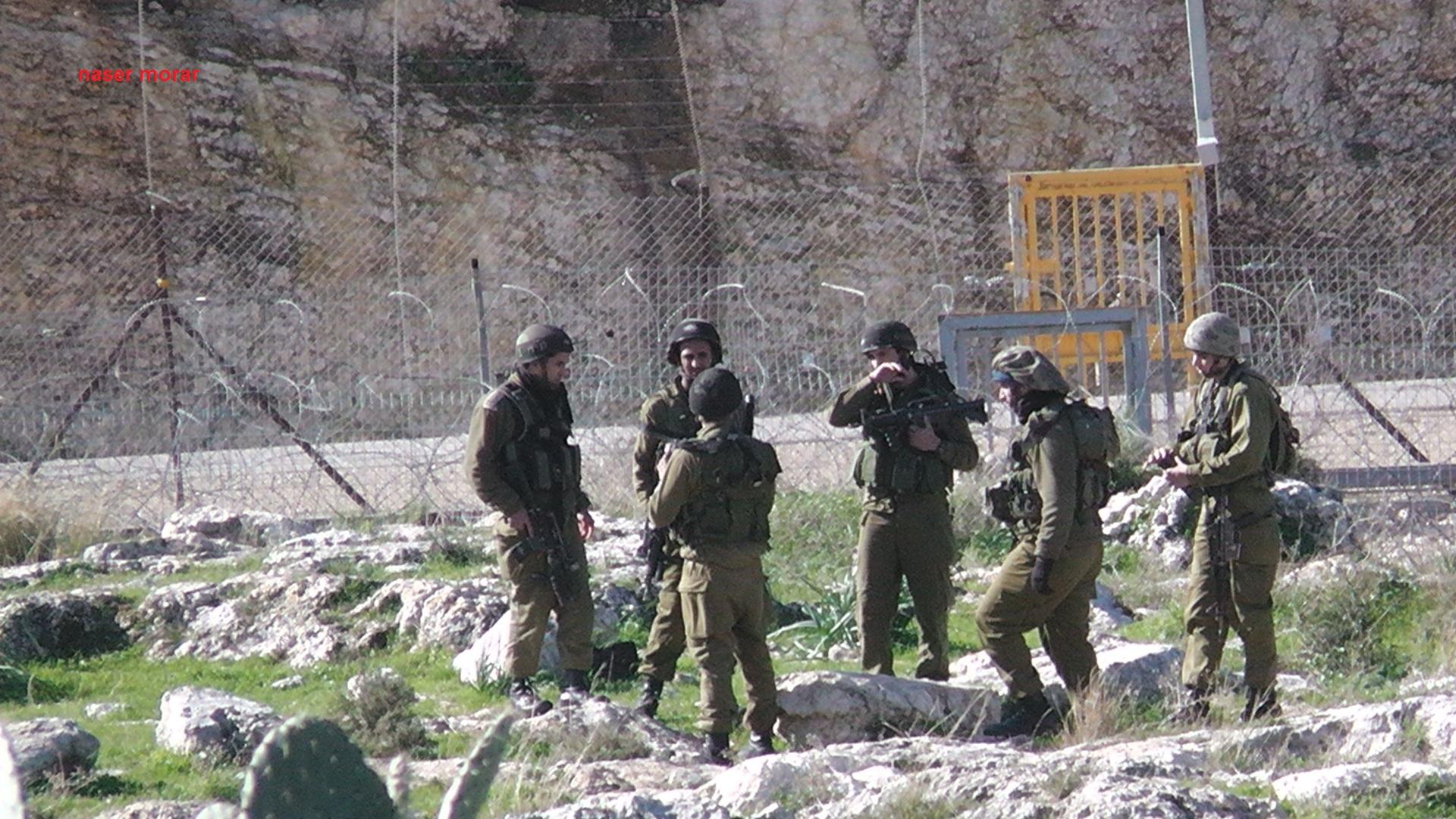 חיילים בזירה לאחר שהנער סמיר עווד נורה בגבו קרוב לגדר ההפרדה, בודרוס (נסאר מוראר, בצלם)
