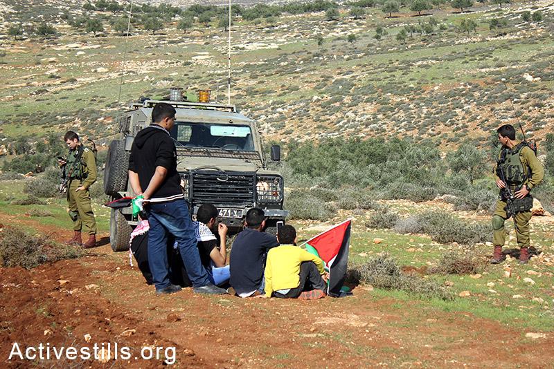 חקלאים פלסטינים יושבים ליד ג׳יפ צבאי במהלך פעולה ישירה לחרישת אדמות, הכפר סלמה, הגדה המערבית, 5 דצמבר, 2014. אחמד אל-באזז/אקטיבסטילס