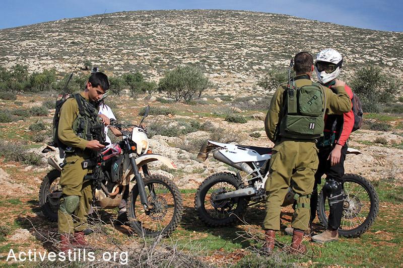 חייל ישראלי מבקש ממתנחל להימנע מנסיעה על האדמות החקלאיות של הכפר, הגדה המערבית, 5 דצמבר, 2014. אחמד אל-באזז/אקטיבסטילס