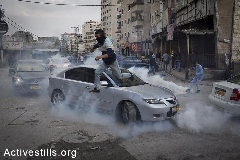 צעיר פלסטינים רץ מגז מדמיע שנורה על ידי שוטרים במהלך הפגנה במחנה הפליטים שועפט, מזרח ירושלים, 5 לנובמבר, 2014. (אורן זיו/אקטיבסטילס)