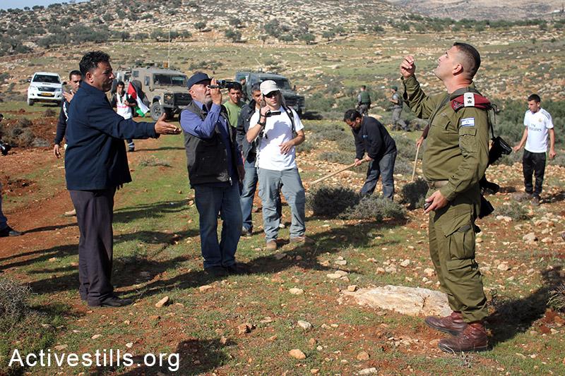 חקלאים פלסטינים מתווכחים על חיילים במהלך פעולה ישירה לחרישת אדמות, הכפר סלמה, הגדה המערבית, 5 דצמבר, 2014. אחמד אל-באזז/אקטיבסטילס