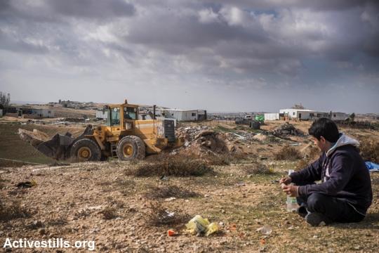 תושב הכפר סעוה צופה בבולדוזר הורס בתים בכפר, 23.12.2014. (יותם רונן/אקטיבטילס)