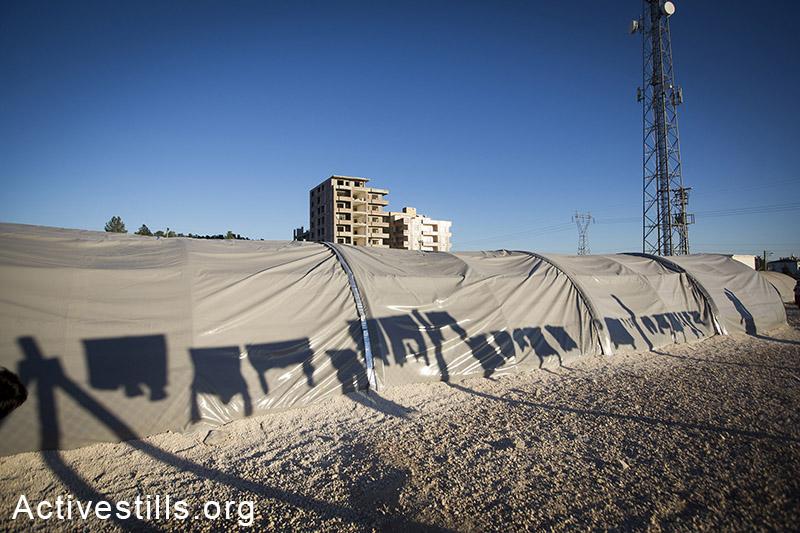 צל כביסה תלויה במחנה הפליטים רוג׳אווה שבעיר סורוק. הפליטים, סורים וכורדים, הגיעו מהעיר קובאני בסוריה, טורקיה, אוקטובר 2014. תמונה: פאיז אבו-רמלה/אקטיבסטילס