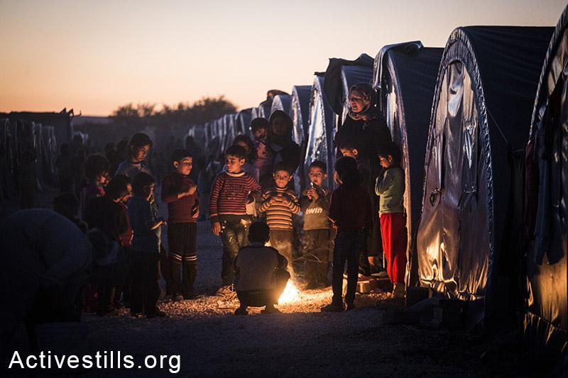 פליטים מתחממים ליד מדורה במחנה הפליטים במחנה הפליטים ארין מירקסאם שבעיר סורוק, טורקיה, אוקטובר 2014. תמונה: פאיז אבו-רמלה/אקטיבסטילס