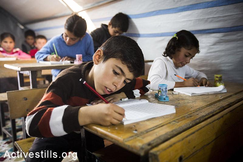 ילדים לומדים בבית ספר שמופעל על ידי מתנדבים בינלאומיים, במחנה הפליטים רוג׳אווה שבעיר סורוק, טורקיה, אוקטובר 2014. תמונה: פאיז אבו-רמלה/אקטיבסטילס