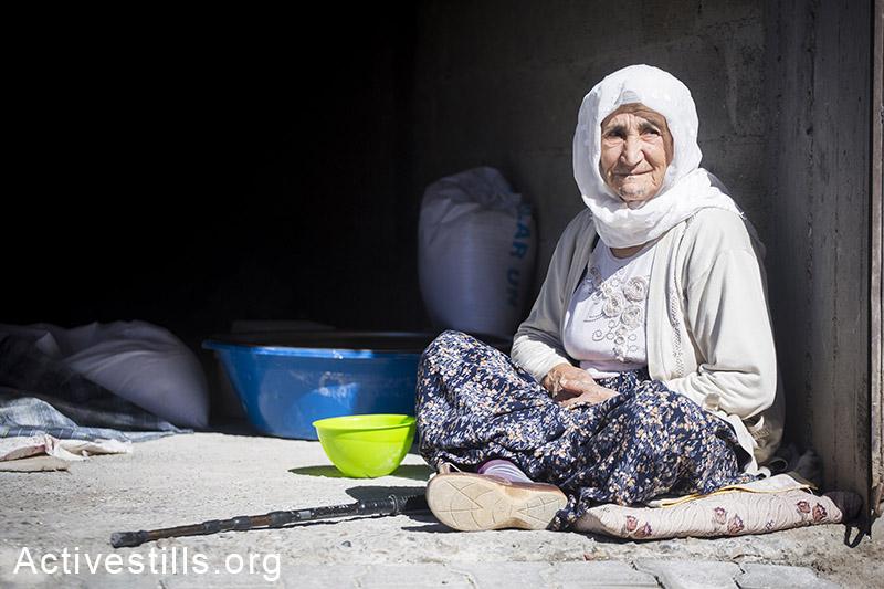 פליטה כורדית שברחה מהעיר קובאני שברחה מן העיר קובאני שבסוריה יושבת במבנה אותו השמישו פליטים למגורים, העיר סורוק, תורכיה, אוקטובר, 2014. תמונה: פאיז אבו-רמלה/אקטיבסטילס