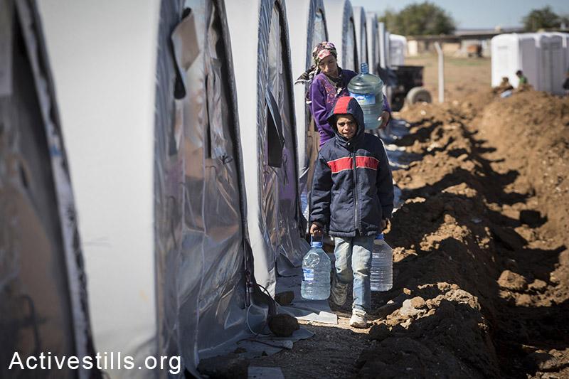 משפחה סוחבת בקבוקי מים במחנה הפליטים ארין מירסקאם, גבול טורקיה-סוריה, אוקטובר, 2014. במחנה אין מים זורמים, והפליטים לוקחים מים מחקלאים או מתחנות דלק באזור. תמונה: פאיז אבו-רמלה/אקטיבסטילס