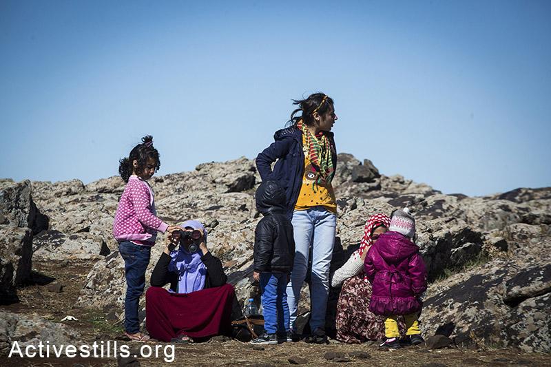 פליטים בשרחו מהעיר קובאני מסתכלים על האזור ממנו ברחו, באזור גבול סוריה-טורקיה, אוקטובר 2014. מידי יום מגיעים מאות לגבול להביט על העיר שהשאירו מאחור, וצופים בפיצוצים ובקרוב בעזרת משקפות. חלקם מצליחים בלילה לחזור לקובאני ולצאת לפנות בבוקר. תמונה: פאיז אבו-רמלה/אקטיבסטילס