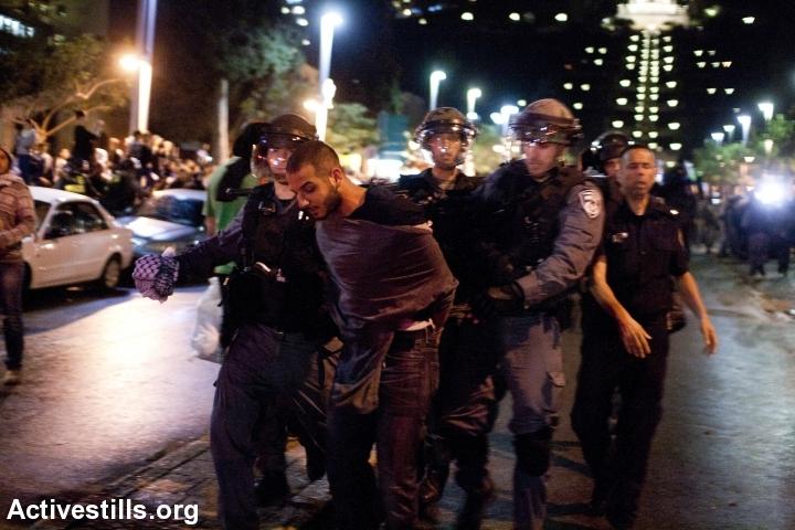 שוטרים עוצרים מפגין בהפגנה נגד תוכנית פראוור, חיפה, נובמבר 13' (קרן מנור / אקטיבסטילס)