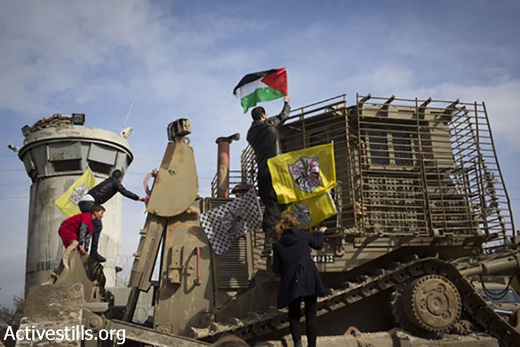 מפגינים מטפסים על דחפור ה- D9 ומציבים עליו דגל פלסטין. 2 בינואר, 2015. (אורן זיו/אקטיבסטילס)