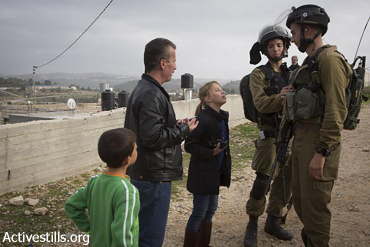 באסם תמימי וביתו מתווכחים עם החיילים שנכנסו לכפר. 2 בינואר, 2015. (אורן זיו/אקטיבסטילס)