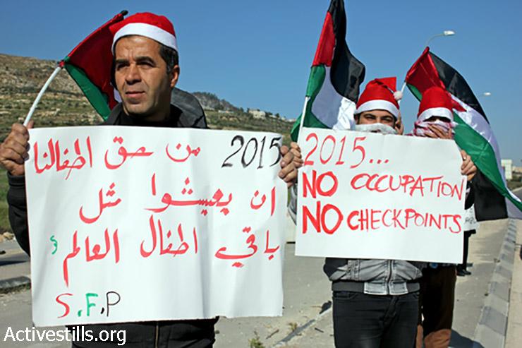 פעילים נושאים שלטים עם משאלותיהם לשנה החדשה- שנת 2015 ללא כיבוש וללא מחסומים, 1 בינואר, 2015. (אחמד אל-באז/אקטיבסטילס)