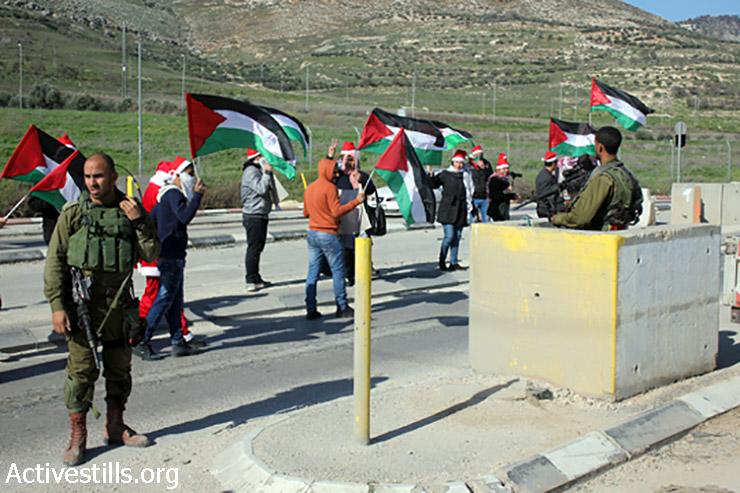 מפגינים מניפים דגלי פלסטין במחסום חווארה, 1 בינואר, 2015. (אחמד אל-באז/אקטיבסטילס)