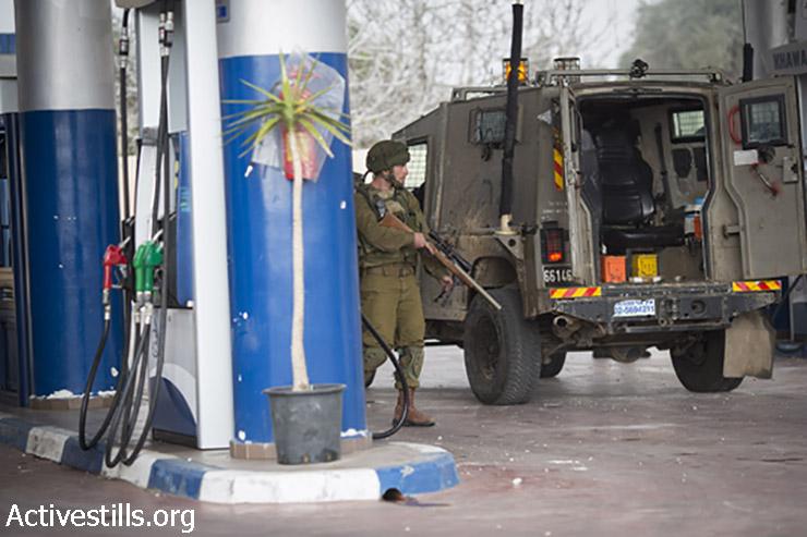 צלף עומד בתחנת הדלק בעת הפלישה לכפר. 2 בינואר, 2015. (אורן זיו/אקטיבסטילס)