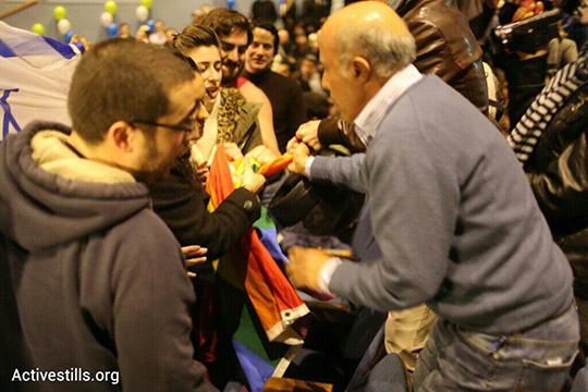 אחראי ביטחון של אוניברסיטת תל אביב מנסה לחטוף דגל גאווה מפעילות להטבקיות במהלך הכנס. (אקטיבסטילס)
