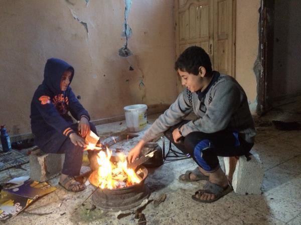 ילדים מתחממים אתמול במה שנותר מביתם בסוג'עיה , עזה. צילום: Dan Cohen