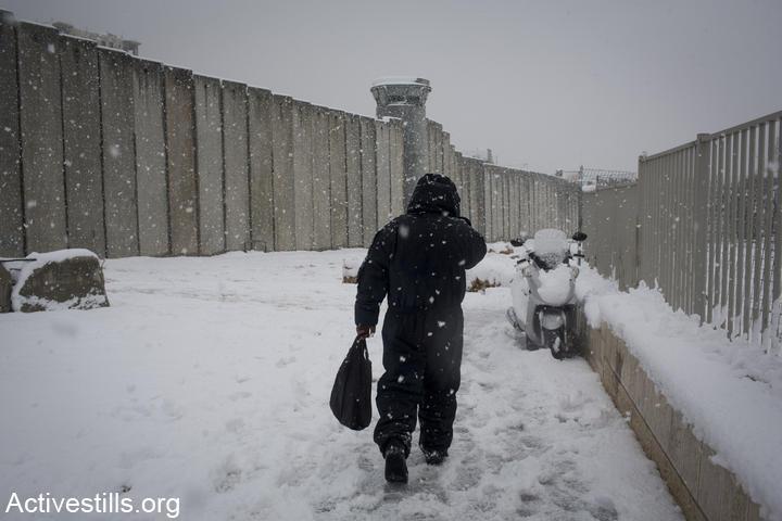 פועל פלסטיני חוצה מחסום בשלג (אורן זיו / אקטיבסטילס)