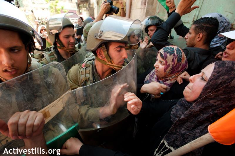 נשים פלסטיניות מפגינות ביום הנכבה, ומולן חיילים. חברון, 2012 (ריאן רודריק ביילר / אקטיבסטילס)