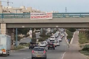 שלט תמיכה בשוטר היורה מתחנת רהט שנתלה על גשר הרכבת בשכונת רמות בבאר שבע. (צילום: חיה נח, פורום דו-קיום בנגב לשוויון אזרחי)