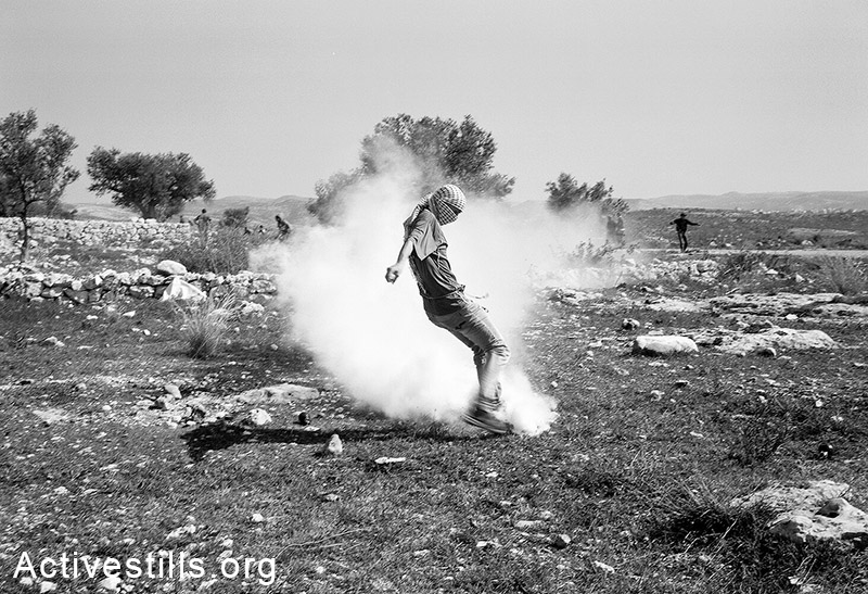 נער בועט חזרה בגז מדמיע במהלך הפגנה בבילעין, הגדה המערבית, 2014. מיקי קרצמן / אקטיבסטילס